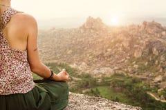 Kvinna som mediterar på det steniga berget på soluppgång, Indien Arkivfoton