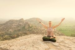 Kvinna som mediterar på det steniga berget på soluppgång, Indien Royaltyfria Foton