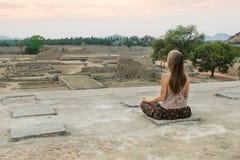Kvinna som mediterar på det steniga berget på soluppgång, Indien Royaltyfri Bild