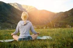 Kvinna som mediterar på gräs med berg i bakgrunden Arkivfoto