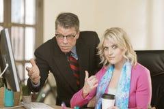 Kvinna som misshas med den manliga kollegan Arkivfoton