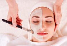 Kvinna som mottar den ansikts- maskeringen på skönhetsalongen Royaltyfri Foto