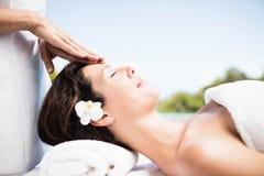 Kvinna som mottar en head massage från massör royaltyfri fotografi