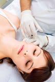 Kvinna som mottar en injektion av botox från en docto Royaltyfri Foto