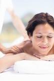 Kvinna som mottar en tillbaka massage från massör arkivbild