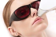 Kvinna som mottar epilation för laser-hårborttagning på framsida begrepp för laser-hudomsorg Royaltyfria Foton