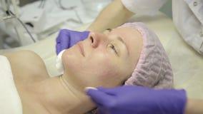 Kvinna som mottar Spa behandling Framsida för massöslokalvårdkvinna med bomullsbomullstoppar på brunnsorten lager videofilmer
