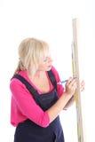 Kvinna som mäter en längd av trä Fotografering för Bildbyråer