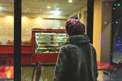 Kvinna som mycket ser det mysiga bagerifönstret av olika kakor på en vinternatt Arkivfoto