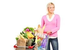 Kvinna som mycket skjuter en shoppingvagn av livsmedel Royaltyfri Fotografi