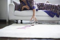 Kvinna som når in mot spillt vinexponeringsglas på filten Arkivfoto