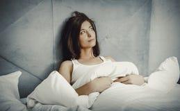 Kvinna som ner hemma ligger på henne underlag Arkivbilder