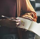 Kvinna som ner skriver på en tom notepad arkivfoto