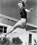 Kvinna som netto hoppar över en tennis (alla visade personer inte är längre uppehälle, och inget gods finns Leverantörgarantier s Fotografering för Bildbyråer