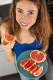 Kvinna som nytt har klippt grapefruktskivor Arkivfoto