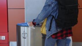 Kvinna som offentligt kastar avskräde in i avfallasken med pappers- plast- och för exponeringsglastecken ställe och lämna F?rlora stock video