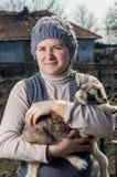 Kvinna som omfamnar en goatling. Arkivfoton