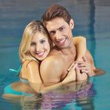 Kvinna som omfamnar mannen i simbassäng Royaltyfria Bilder