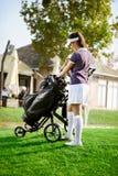 Kvinna som ordnar din golfutrustning Royaltyfri Bild