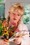Kvinna som ordnar fallblommor Arkivfoton