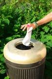Kvinna som ordnar silkespapperpapper i Trashcan Arkivfoto