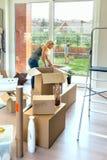 Kvinna som packar upp flyttande askar royaltyfria bilder