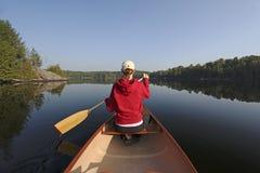 Kvinna som paddlar en kanot på en nordlig Ontario sjö Arkivbild