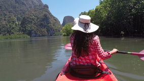 Kvinna som paddlar kayaking i den härliga lagunhandlingkameran pov av flickasammanträde på kajakfartyget lager videofilmer