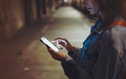 Kvinna som pekar fingret på skärmsmartphonen på ljus för bakgrundsbelysningbokeh i den atmosfäriska staden för natt, hipster som  arkivbilder