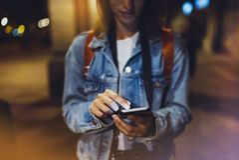 Kvinna som pekar fingret på smartphonen för tom skärm på bakgrundsbokehljus i atmosfärisk stad för natt, använda för bloggerhipst royaltyfri foto