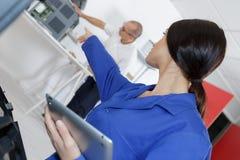 Kvinna som pekar och ger anvisningar till den höga kollegan arkivfoto