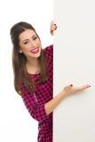 Kvinna som pekar på det tomma tecknet Fotografering för Bildbyråer