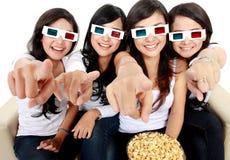 Kvinna som pekar till TV, medan hålla ögonen på filmen 3d Royaltyfri Bild