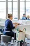 Kvinna som placeras på bärbar datoruppladdningsstationen i en flygplats Royaltyfri Foto