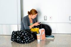 Kvinna som placeras på golvet som laddar hennes telefon i en flygplats Arkivfoton
