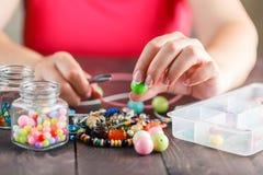 Kvinna som planlägger den färgrika halsbandet med plactic pärlor Royaltyfri Bild