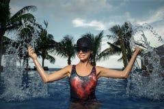 Kvinna som plaskar i blå simning Arkivfoton