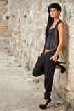Kvinna som plattforer vid en stenvägg Fotografering för Bildbyråer