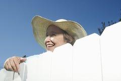 Kvinna som plirar över det trädgårds- staketet royaltyfria bilder