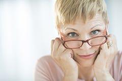 Kvinna som plirar över hennes glasögon Royaltyfria Bilder