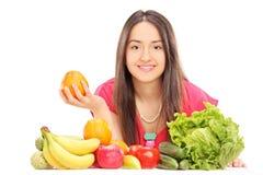 Kvinna som poserar bak frukter och grönsaker Royaltyfria Foton