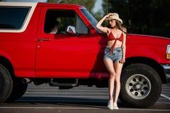 Kvinna som poserar bredvid den klassiska bilen Arkivfoto