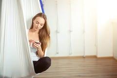 Kvinna som poserar i anti--gravitation flyg- yogahängmatta koppla av med telefonen fotografering för bildbyråer