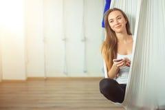 Kvinna som poserar i anti--gravitation flyg- yogahängmatta koppla av med telefonen royaltyfri bild