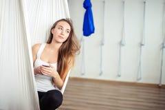 Kvinna som poserar i anti--gravitation flyg- yogahängmatta koppla av med telefonen royaltyfri fotografi