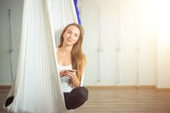 Kvinna som poserar i anti--gravitation flyg- yogahängmatta koppla av med telefonen royaltyfria bilder