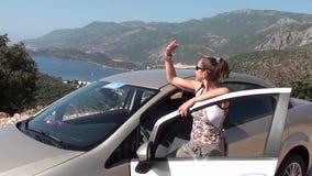 Kvinna som poserar med bilen lager videofilmer