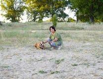 Kvinna som poserar med den amerikanska staffordshire terrierhunden på stranden Fotografering för Bildbyråer