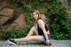 Kvinna som poserar med en skateboard Royaltyfria Bilder
