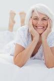 Kvinna som poserar, medan hon ligger på säng Arkivbilder